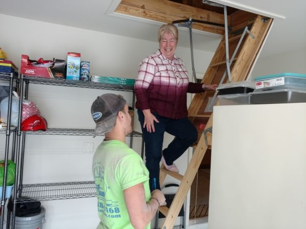 Woman On Attic Stairs Smiling at Contractor
